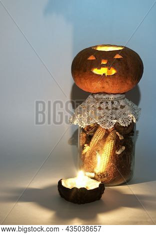 Jack O Lantern On Large Glass Jar Of Dried Corn On The Cob And Corn Stigmas. At The Candle Holder Wi