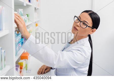 Asian Pharmacist In Glasses Reaching Medication In Drugstore