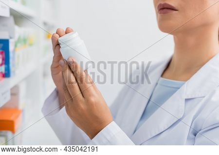 Partial View Of Pharmacist In White Coat Holding Bottle With Medication