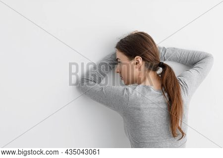 Unhappy Worried Caucasian Millennial Lady Suffering From Depression, Leaning Against White Wall At H