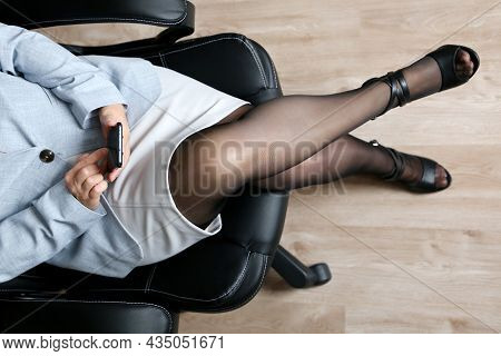 Woman Using Smartphone In Office, Online Communication, Text Messaging. Lady In White Leather Skirt