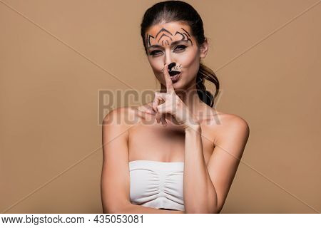 Young Woman With Bare Shoulders And Tiger Makeup Showing Hush Sign Isolated On Beige