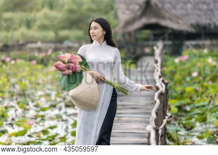 Portrait Of Beautiful Vietnamese Woman With Traditional Vietnam Hat Holding The Pink Lotus Walking O