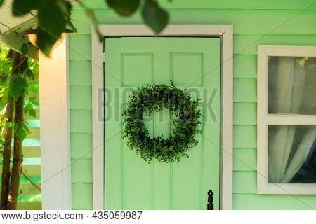 Closeup Of Green Door And Decorative Wreath. Autumn Welcome Wreath, Decorating Front Door Home. Hous