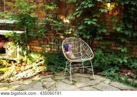 Wooden Armchair Standing On Backyard With Foliage, Copy Space. Interior Autumn Patio. Wicker Rattan