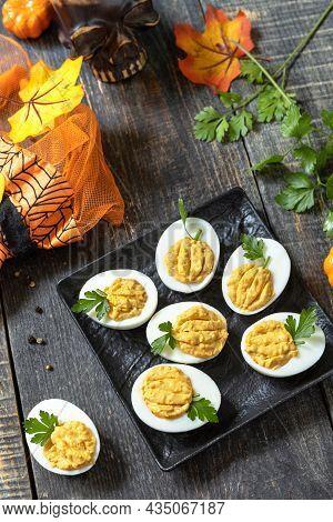 Halloween Funny Idea For Party Food. Halloween Creative Set Stuffed Eggs Pumpkin On A Wooden Table.