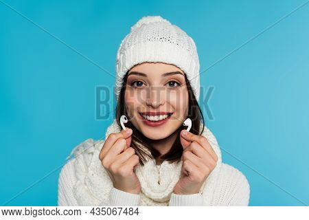 Pretty Woman In Knitted Hat And Scarf Holding Wireless Earphones Isolated On Blue