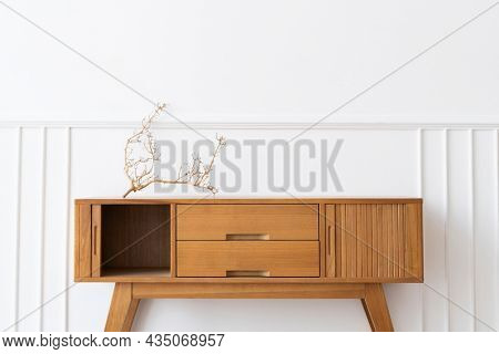 Wooden sideboard table against a white wall