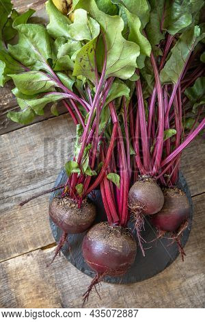 Fresh Organic Ripe Juicy Beetroot On A Wooden Kitchen Table. The Concept Of Organic Nutrition And Au