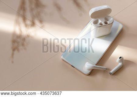 Wireless Technology, Modern Tech. Minimal Shot Smartphone And Of A Pair Of White Wireless Headphones