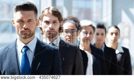 Multi Ethnic Group Of Business People Standing In A Row In Modern Office Bluilding Delective Focus O
