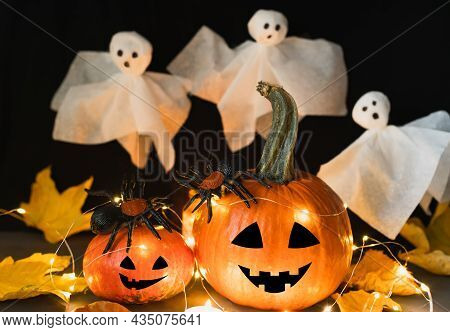 Halloween Pumpkins With Funny Faces And White Ghosts On A Dark Background. Festive Decor For Hallowe