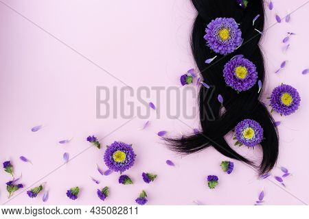 Pigtail From Dark Hair With Fresh Lilac Flowers In It. Hair Care Concept.