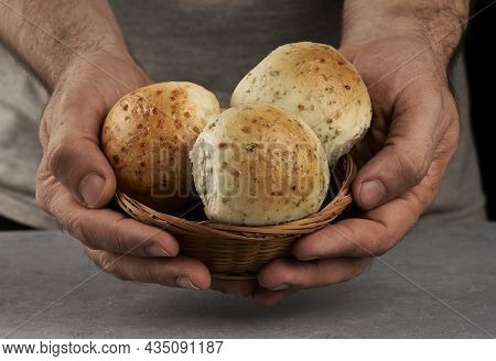 Man's Hands Offering Flavored Breads In A Basket