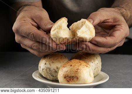 Man's Hand Breaking Piece Of Flavored Bread