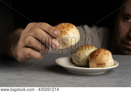 Man Placing Flavored Breads On A Plate