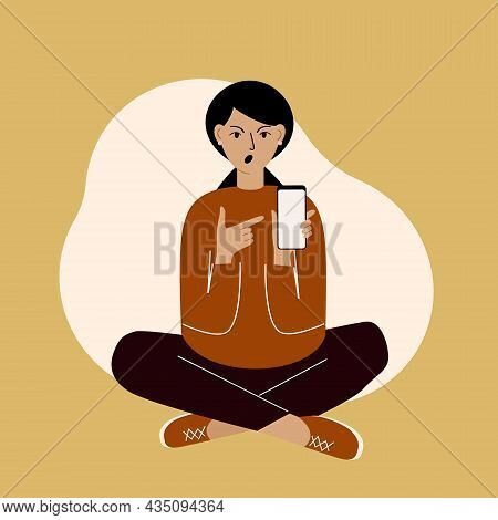 Young Woman On The Phone Sitting Cross-legged And Points Finger At The Phone Screen