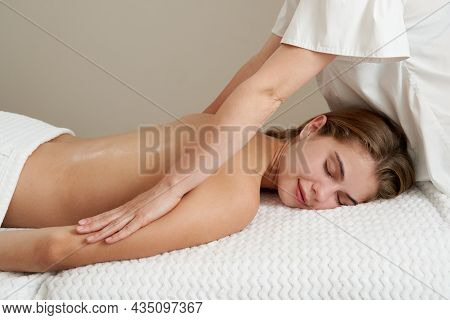 Masseur Massaging Young Woman On Massage Table In Spa Salon. Young Woman Relaxing During Back Massag