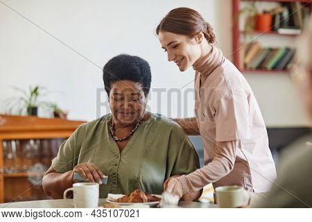 Portrait Of Smiling Young Woman Caring For Senior African-american Lady In Nursing Home, Copy Space