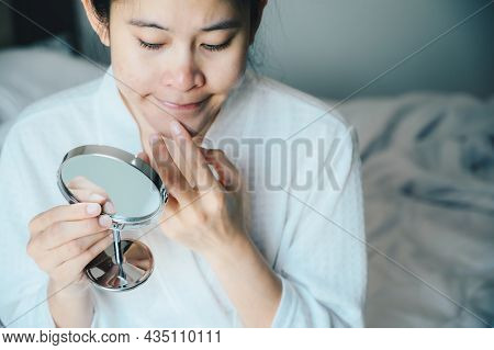 Young Asian Woman Worry About Her Face When She Saw The Problem Of Acne And Scar By The Mini Mirror.