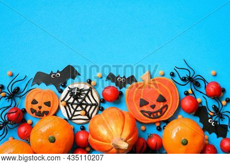 Halloween Background With Cookies, Spiders And Bats, Top View. Halloween Funny Objects On Blue Table