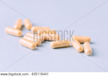 Coenzyme Q10 Capsules. Dietary Supplements. Bright Paper Background. Close Up.