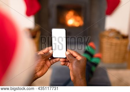 Back view of african american senior man using smartphone with copy space at christmas time. retirement lifestyle, christmas festivities and communication technology.