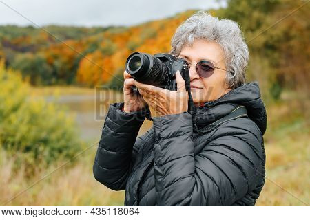 Senior Woman With Glasses Using Digital Camera, Retired Woman Photographing Autumn Landscape In Fron