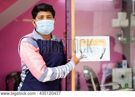 Barber With Medical Mask Showing Wear Mask At Saloon Sign Board To Avoid Coronavirus Or Covid-19 Inf