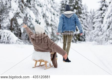 Back View Of  Man Pulling Sledge With Joyful Woman In Winter Forest