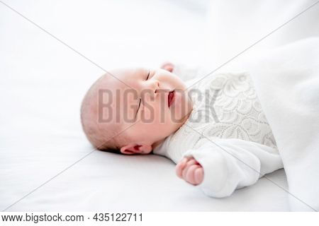 Adorable newborn baby girl wearing white costume lying in the bed and sleeping with mouth open. Cute infant child napping at home
