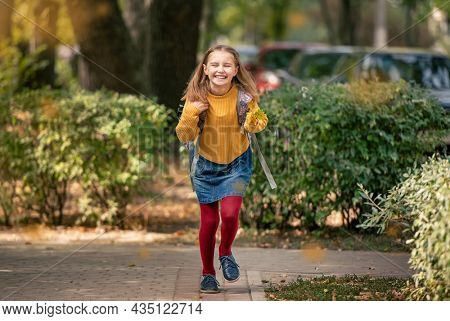 Preteen school girl with backpack holding yellow leaves in her hand, running and smiling. Pretty pupil female kid having fun in autumn park after lessons