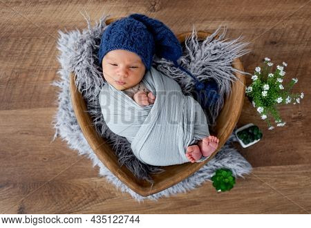 Adorable newborn baby boy swaddled in fabric and wearing cute knitted hat falling asleep during studio photoshoot in wooden heart shape bed. Infant child napping