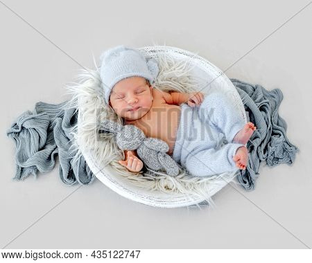 Adorable newborn baby boy wearing cute knitted hat and pants sleeping in wooden basin on fur and holding handmade bunny toy. Infant child napping