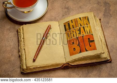 think and dream big motivational phrase -  word abstract in letterpress wood type printing blocks in a retro journal with a cup of tea