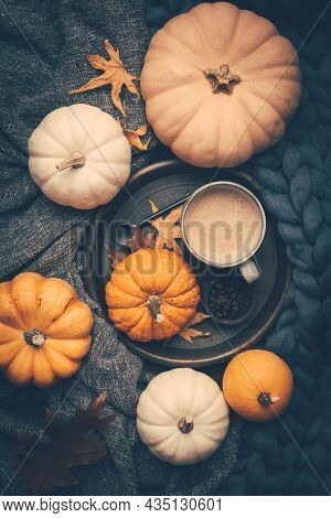 Autumn flat lay with cup of coffee, pumpkins and cuddle blanket on wooden background