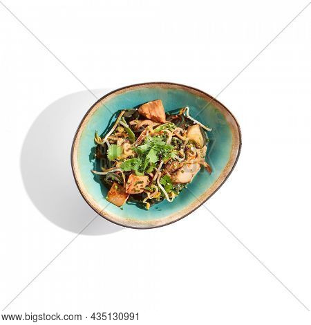 Pan asian food - chicken udon with mushrooms on white background. Noodle with chicken  on wok in asian style. Indonesian wok with black udon noodles and chicken in ceramic bowl