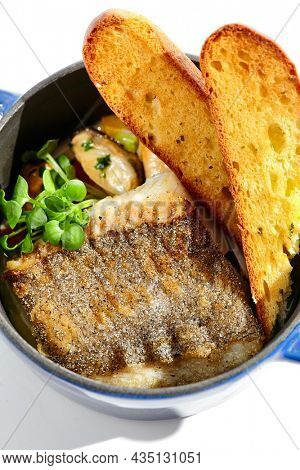 Seafood stew with roast cod and crispy ciabatta. Mussels tomato soup with  fish and roast bread. Cioppino ragu with cod. Brazilian moqueca. Fish with crispy skin and seafood ragu in blue pot
