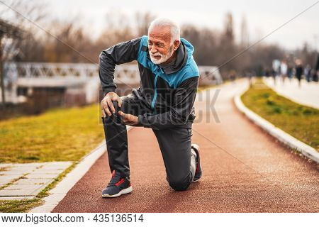 Active Senior Man Is Having Pain In Knee While Jogging.