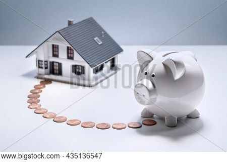 Saving to buy a house, piggy bank with coin trail leading to model home