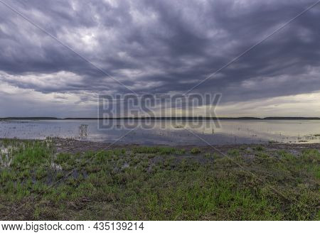 Evening Landscape On The Lake In Early Spring. The Dramatic Sky Is Reflected In The Lake. Young May