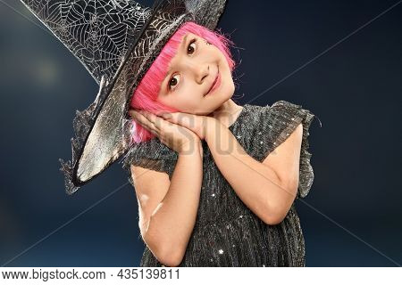 Happy Halloween. Studio portrait of a lovely little girl with a charming smile in a witch costume and bright pink wig posing on a dark background.