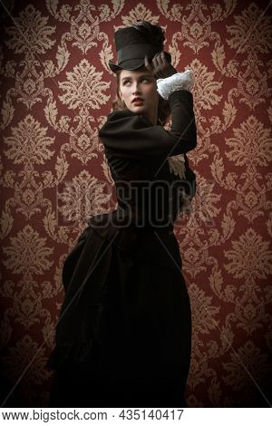 Portrait of a beautiful elegant lady in a 19th century suit posing on a vintage background. 19th century fashion and beauty.