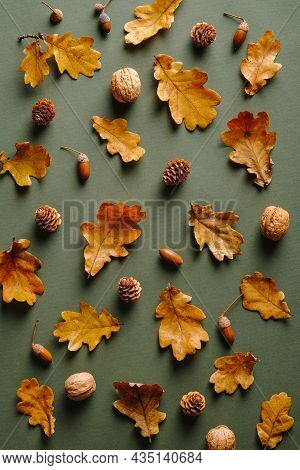 Autumn Pattern With Dry Oak Leaves, Acorns, Walnuts, Pine Cones On Green Background. Vintage Style.