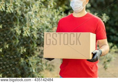 Delivery Man Holding Cardboard Boxes On The Farm In Medical Gloves And Protective Mask. Online Shopp