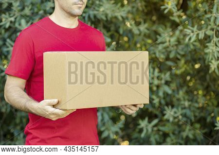 Delivery Man Holding Cardboard Boxes On The Farm. Online Shopping And Express Delivery Courier Order