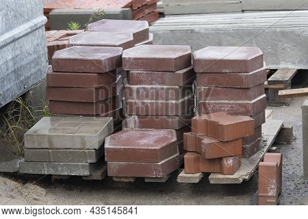 Stacks Of Red Paving Slabs On Wooden Pallet At Construction Site. Diversify Assortment Samples Of Pa