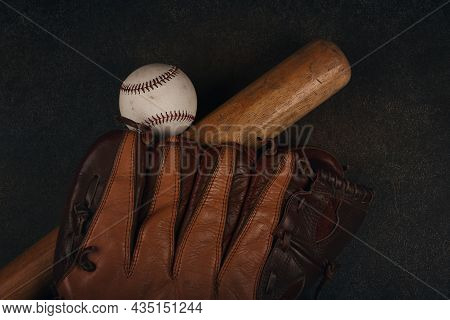 Close Up One Old Baseball Ball, Wooden Bate And Worn Leather Vintage Glove On Grunge Dark Brown Back