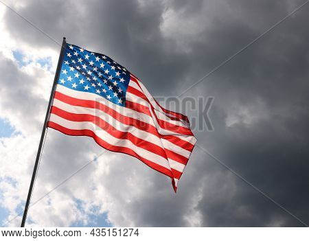 Backlit Us National Flag Flying And Waving In The Wind Over Gray Stormy Cloudy Sky, Symbol Of Americ