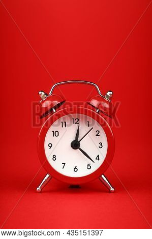 Close Up One Small Red Metal Twin Bell Retro Alarm Clock Over Red Paper Background With Copy Space,